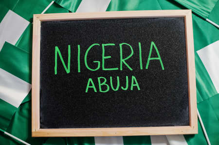 Happy independence day of Nigeria, Abuja. Text on board with nigerian flags.