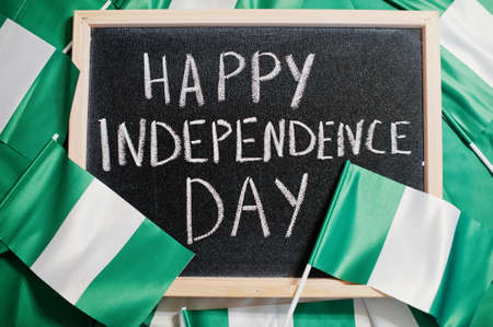 Happy independence day of Nigeria. Text on board with nigerian flags.