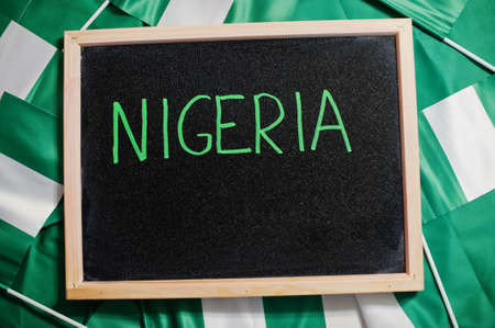 Happy independence day of Nigeria. Text on board with nigerian flags. Imagens