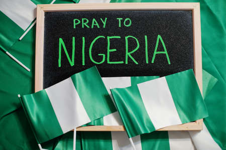 Pray to Nigeria. Text on board with nigerian flags. Imagens