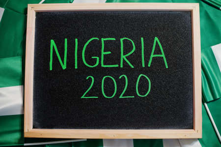 Happy independence day of Nigeria 2020. Text on board with nigerian flags.