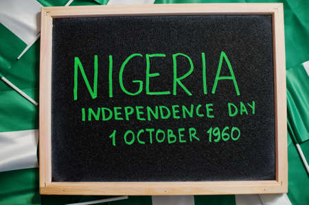 Happy independence day of Nigeria. 1 October 1960. Text on board with nigerian flags.