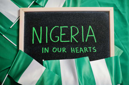 Nigeria in our hearts. Text on board with nigerian flags.