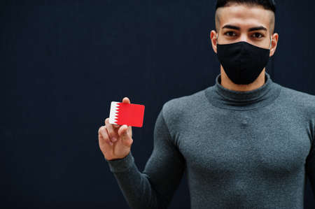 Middle eastern man in gray turtleneck and black face protect mask show Bahrain flag isolated background.