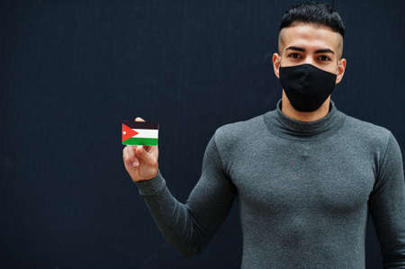 Middle eastern man in gray turtleneck and black face protect mask show Jordan flag isolated background.