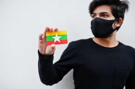 Asian man wear all black with face mask hold Myanmar flag in hand isolated on white background. Coronavirus country concept. 스톡 콘텐츠