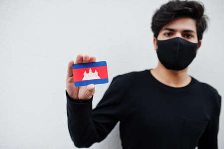 Asian man wear all black with face mask hold Cambodia flag in hand isolated on white background. Coronavirus country concept.