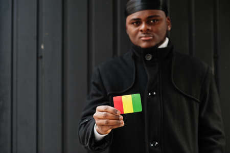 African man wear black durag hold Guinea flag at hand isolated dark background.