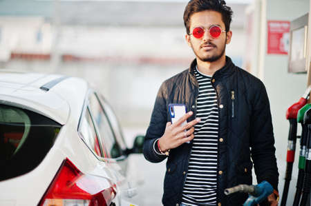 South asian man or indian male refueling his white car on gas station with mobile phone at hand.