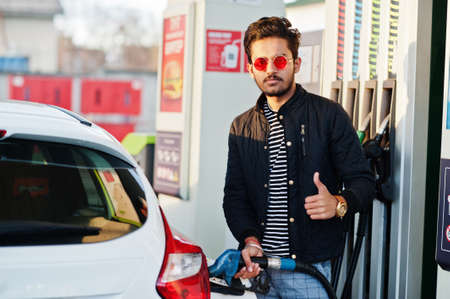 South asian man or indian male refueling his white car on gas station.
