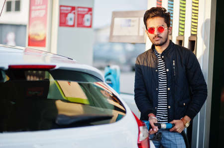 South asian man or indian male refueling his white car on gas station. Standard-Bild