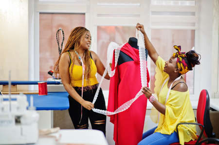 Two african dressmaker woman designed new red dress on mannequin at tailor office. Black seamstress girls. Archivio Fotografico