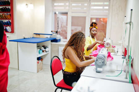 Two african dressmaker woman sews clothes on sewing machine at tailor office. Black seamstress girls.