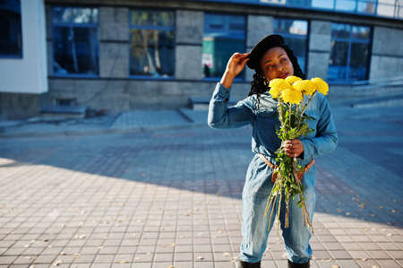 Stylish fashionable african american women in jeans wear and black beret with yellow flowers bouquet posed outdoor in sunny day against blue modern building.