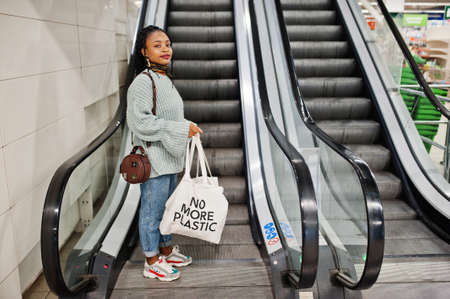 African woman with shopping eco bags on escalator at mall.