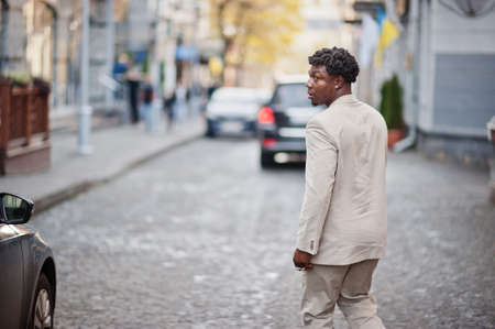 Stylish afro man in beige old school suit. Fashionable young African male in casual jacket on bare torso. Foto de archivo