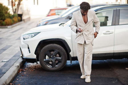 Stylish afro man in beige old school suit against modern hybrid electro suv car. Fashionable young African male in casual jacket on torso.