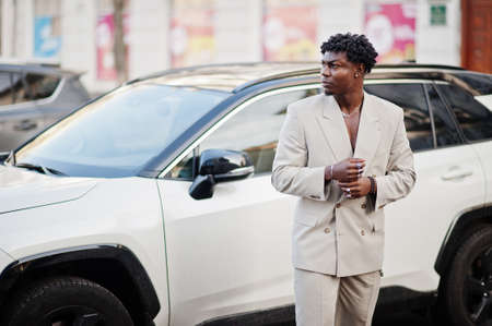 Stylish afro man in beige old school suit against modern hybrid electro suv car. Fashionable young African male in casual jacket on torso. Foto de archivo