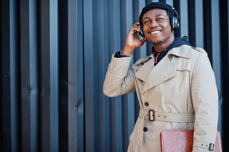 African american man with headphones, wear on hat and coat listening music on steel background.