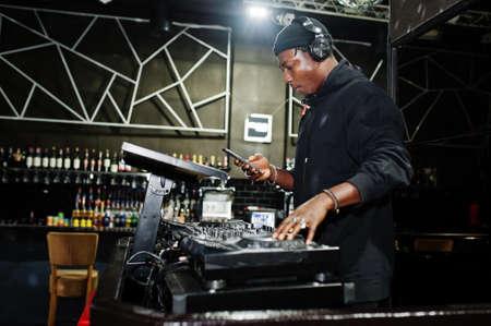 African american dj play music on decks at night club.