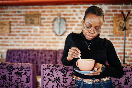 African woman in black sweater and eyeglasses posed at cafe with cup of hot drink.