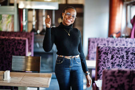 African woman in black sweater posed at cafe and show thumb up by hand.