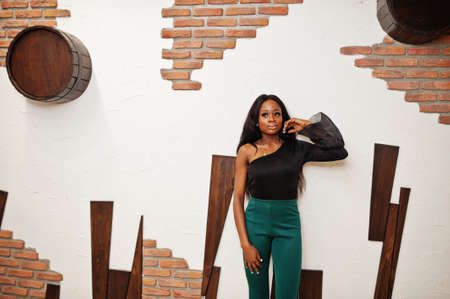 Beauty slim african american model wear on black blouse and green long legs pants posed against wooden wall at pub.