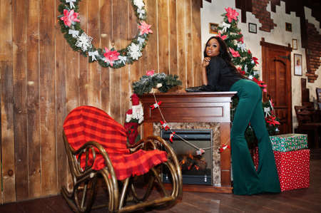 Beauty slim african american model wear on black blouse and green long legs pants posed against christmas mood decorations with wreath, fireplace and rocking chair.