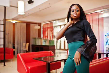 Beauty slim african american model wear on black blouse and green long legs pants posed at chinese cafe.