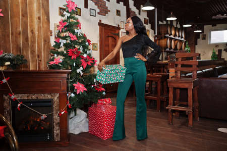 Beauty slim african american model wear on black blouse and green long legs pants posed against christmas mood decorations and hold a gift box for new year celebrations.