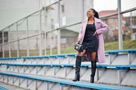 Young stylish beautiful african american woman in street at the stadium bleachers, wearing fashion outfit coat, hold handbag.