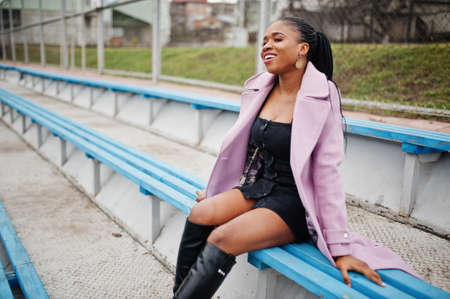 Young stylish beautiful african american woman in street at the stadium bleachers, wearing fashion outfit coat.