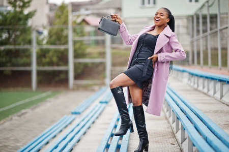 Young stylish beautiful african american woman in street at the stadium bleachers, wearing fashion outfit coat, with handbag.
