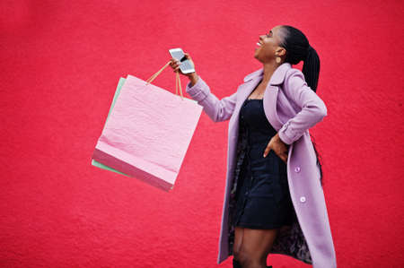 Young stylish beautiful african american woman against red wall background, wearing fashion outfit coat with shopping bags and mobile phone at hands.