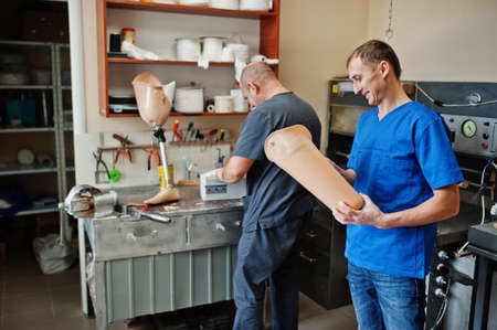 Two prosthetist man workers making prosthetic leg while working in laboratory. Stok Fotoğraf