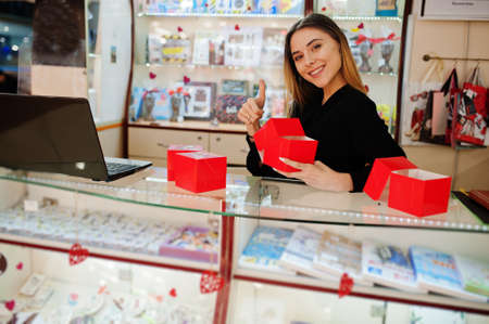 Portrait of young caucasian female woman seller hold red gift boxes. Small business of candy souvenirs shop.