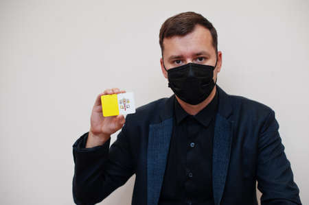 European man wear black formal and protect face mask, hold Vatican City flag card isolated on white background. Europe coronavirus Covid country concept.