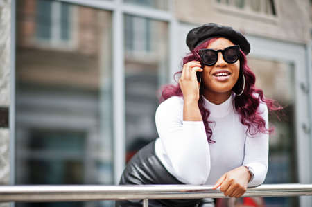 Big mama plus size african american model in black sunglasses, beret and leather skirt posed outdoor and speaking by phone.