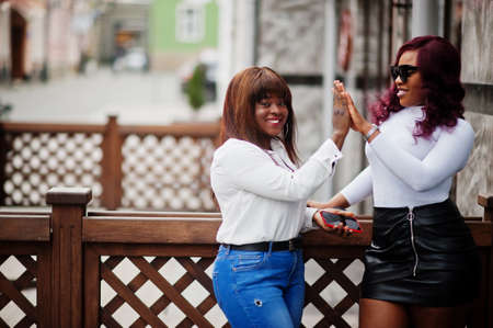 Two female friends african american models posed outdoor with mobile phone at hand.