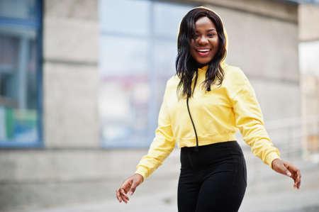 Hipster african american girl wearing yellow hoodie posing at street.
