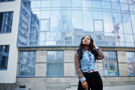 Hipster african american girl wearing jeans shirt with leopard sleeves posing at street against modern office building with blue windows.