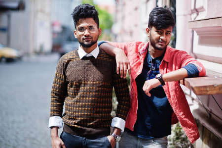 Two young stylish indian man frieds model posing in street.