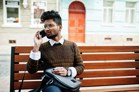 Portrait of young stylish indian man model pose in street, sitting on bench with handbag and smartphone.