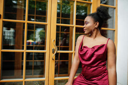 Portrait of a beautiful natural young African woman with afro hair. Black model in red silk dress. Stock Photo