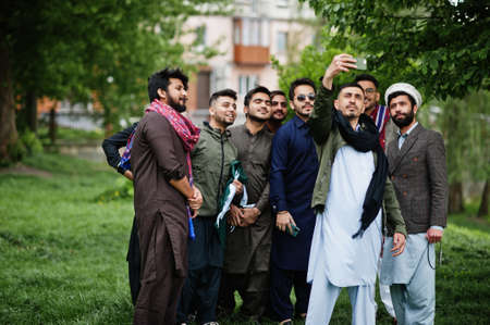 Group of pakistani man wearing traditional clothes salwar kameez or kurta making selfie on mobile phone.
