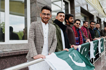 Group of pakistani man wearing traditional clothes salwar kameez or kurta with Pakistan flags.