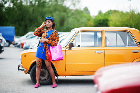 Beautiful african american lady with shopping bags standing near orange classic retro car. Stock fotó