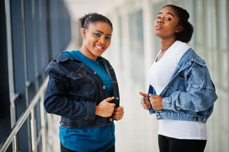 Two african woman friends in jeans jacket posed indoor together.