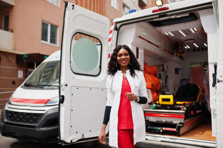 African american female paramedic standing in front of ambulance car.