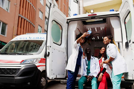 Group of african paramedic ambulance emergency crew doctors making selfie on phone.